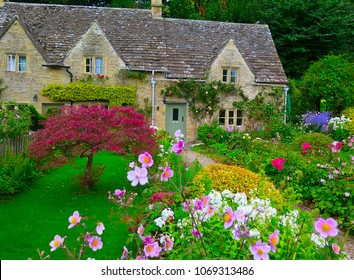Garden and house in UK style. Front of English House. Scenic View of Colourful Flowerbeds and an Attractive English Formal Garden. Exterior of old house with flowers and plants. Properties in UK.