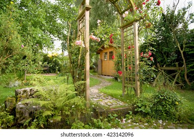Garden idyll with a garden shed and rose arch with blooming red roses