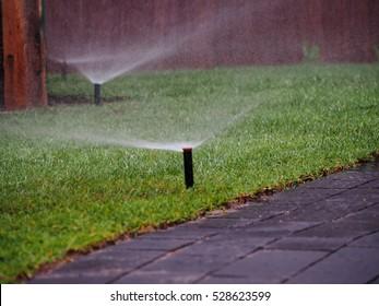 Garden irrigation, working sprinkler. Irrigation system throwing water drops away. Garden irrigation system watering lawn.