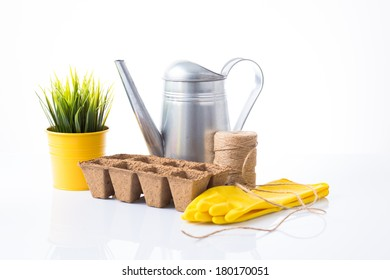 Garden items with green plant over white background
