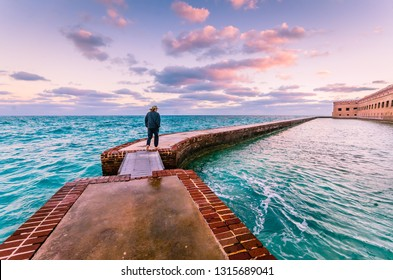 Garden Key, FL / USA - 02-09-2015: Man takes a morning walk on the moat around Port Jefferson at Dry Tortugas National Park in the Florida Keys.