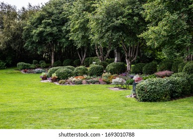 A garden landscape design featuring lawns, trees, evergreen topiary bushes and flower bed