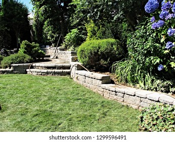 Garden landscape design fresh lawn concrete stone block retaining wall incorporated steps walking path leading to resting area texture background