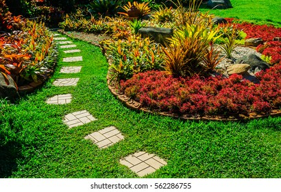 Garden landscape design with pathway intersecting bright green lawns and shrubs white sheet walkway in the garden Landscape design with colorful shrubs, grass with bricks pathways, lawn care service.