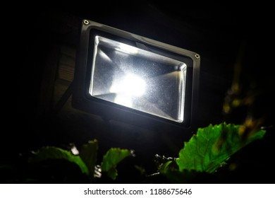 Garden LED spotlight on a wooden building close-up.