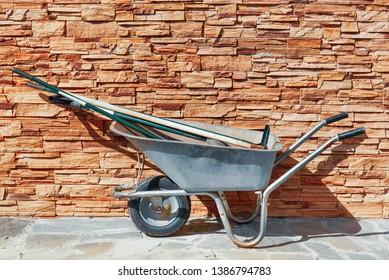 Garden metal wheelbarrow with garden tools. Pushcart.