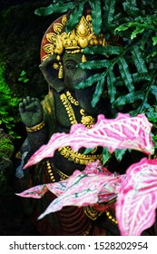 Garden ornaments. Black Indian god statue in a forest park. Ganesha statue hidden behind colored leaves in the public garden.