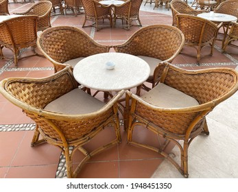 garden and outdoor furniture concept.Set of wooden table and chairs in the street. stoun background. rattan furniture.