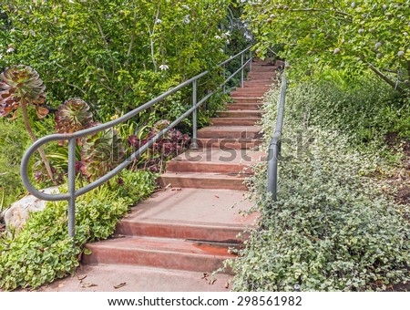 Garden Path Of Red Concrete Steps With Metal Handrails Perspective View.  Damp Steps Surrounded By
