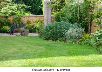 Garden with patio area, lawn and flowerbeds.
