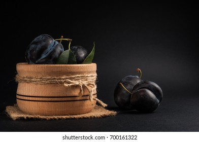 Garden plums in bowl on stone table. View with copy space.