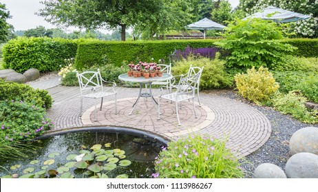 Garden with pond and classic white chairs and table on a patio
