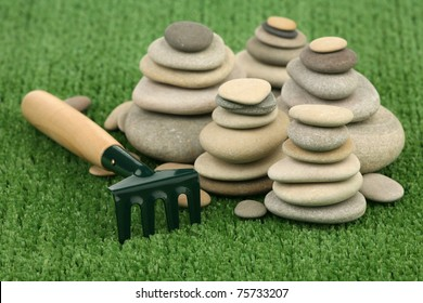 Garden rake and heap of stones on a green background