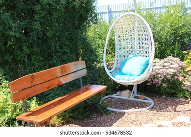 Garden rest area with a hanging swing armchair, benches and a fire pit surrounded by blooming flowers and ornamental shrubs
