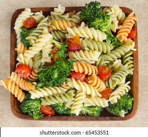 garden rotini salad with broccoli and tomatos closeup in a wooden bowl