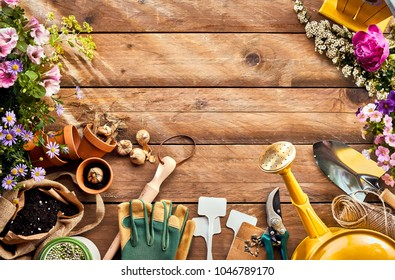 Garden season concept image of flowers and gardening equipment arranged as a frame around wooden surface with lined copy space, viewed from above