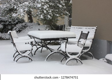 Garden seating area covered with fresh snow in January.