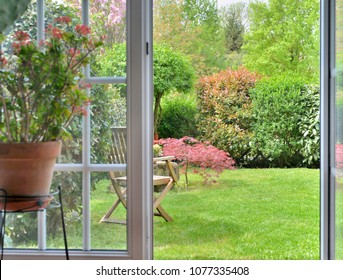 Garden seen by the inside of a house through a door makes windows opened