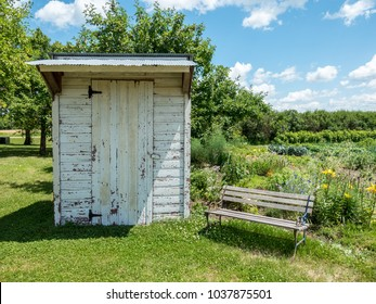 A garden shed and bench in a flower garden.