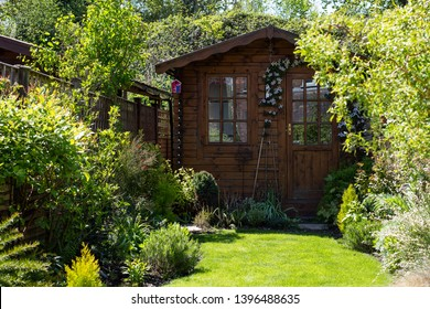 Garden shed at the bottom of a small English cottage garden. It has clematis around the door with various plants in the borders. The lawn is well maintained.
