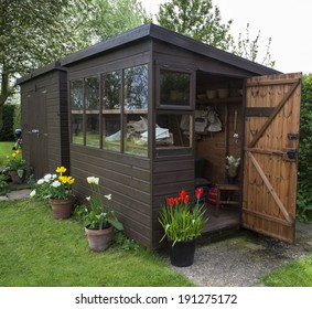 Garden shed exterior in Spring, with shed door open, lawn, tools, flowers, and plant pots.