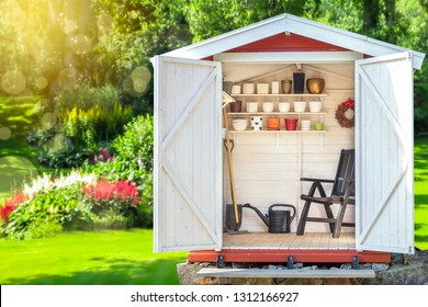 Garden shed filled with gardening tools. Shovels, rake, pots, water pitcher in storage hut. Green sunny garden in the background.
