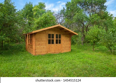 Garden shed. Gardening tools shed. Garden house on lawn in garden. Wooden tool-shed. Hovel made of timber.