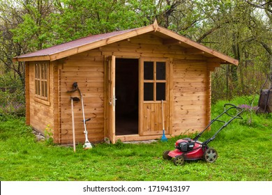 Garden shed with hoe, string trimmer,  rake and grass-cutter. Gardening tools shed. Garden house on lawn in garden. Wooden tool-shed. Hovel made of timber in domestic environment.