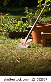 Garden shovel with pots and plants in the background