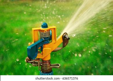 Garden sprinkler head spraying water vintage looking film imitation color correction, instagram-like filter