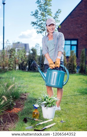 228b34b773d Garden sprinkler. Young beaming gardener wearing comfortable clothes  holding garden sprinkler while watering plants