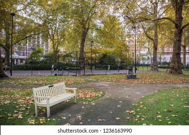 A garden square with bench and tennis courts in London's west end