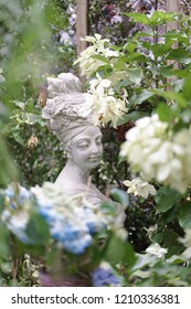 Garden statue. A beautiful stone statue of a woman with a turban and flowers on her hair in the mysteriously secret garden.