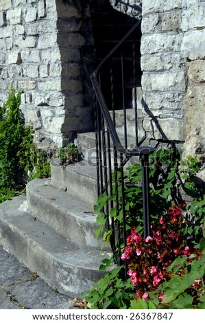 Garden Steps Have Black Iron Handrail And Flowers. Stone Wall In Background.