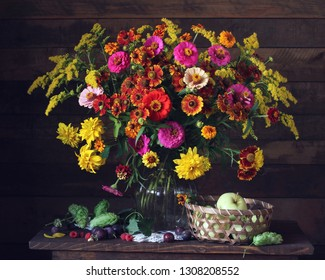 garden still life with flowers, fruits and berries on a dark background. bouquet in a glass vase. raspberry, plum and apples.