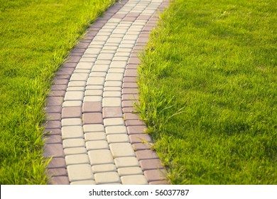 Garden stone path with grass growing up between and around stones, Brick Sidewalk