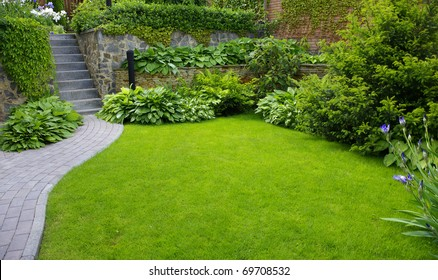 Garden stone path with grass growing up between the stones - Shutterstock ID 69708532