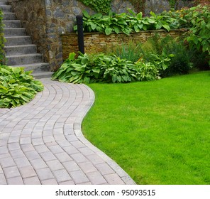 Garden stone path with grass growing up between the stones