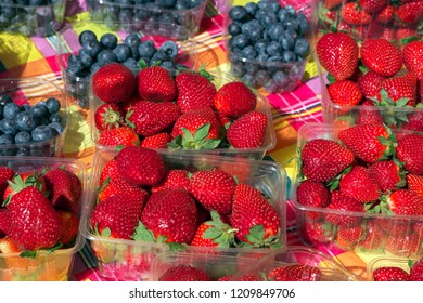 Garden strawberries and cultivated blueberries in small plastic boxes, sold at marketplace.