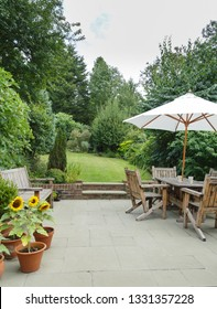 Garden in summer with patio, wooden garden furniture and a parasol or sun umbrella
