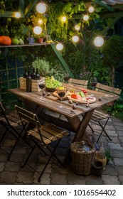 Garden table with appetizers and wine in the evening
