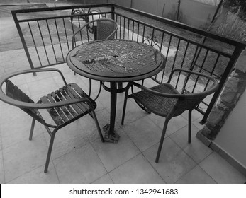Garden table and chairs on patio with black wrought iron railings. Also in monochrome