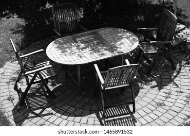 Garden table with four wooden chairs photographed from above