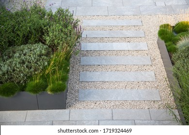 Garden and terrace design with a modern mix of construction material and precious garden decoration objects and various plants