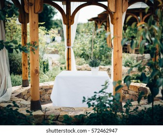 The garden terrace in the oval-shaped with wooden construction and stone foundation, with all around vegetation. Table in the middle with white tablecloth and complemented by a white flower in a pot.
