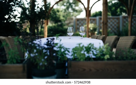 Garden terrace with table and chairs. Table is decorated with pair of glasses and white tablecloth. In the background are seen wooden columns of covering structures, in foreground the potted plants.