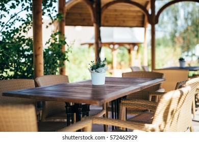 Garden terrace with table and chairs made of natural materials. The table is decorated with flower pot in the middle. In the background are seen plants and wooden columns of covering structures.
