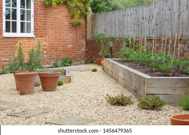 Garden with terracotta plant pots, oak sleeper raised beds and gravel