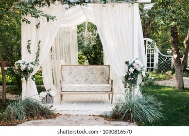 In the garden there is a podium on which a beautiful white sofa in the style of Provence or rustic. Above the sofa is an arch with blossoms and flowing white fabric. Decoration for a wedding, scenery