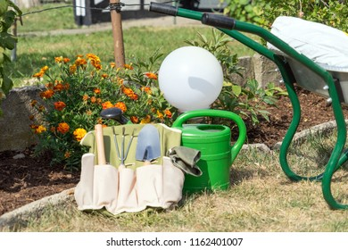 Garden tool and watering can in a garden
